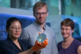 Dr Heping Shen, holding a model of the new type of solar cell developed, along with Dr Daniel Jacobs and Professor Kylie Catchpole from the ANU School of Engineering.